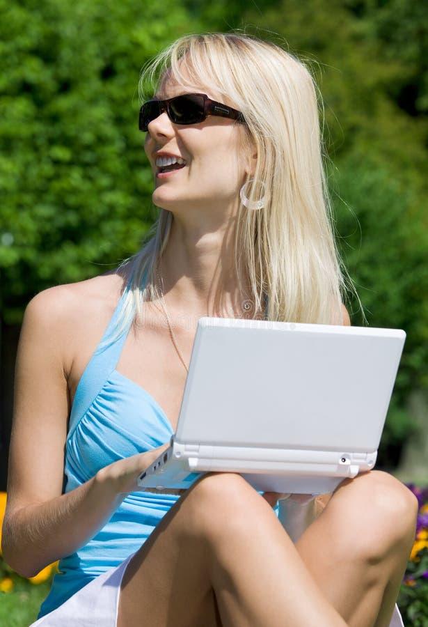 Imagen al aire libre del blonde precioso con el ordenador portátil fotografía de archivo
