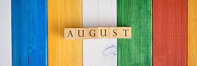 Imagen amplia de la visión de los cubos de madera que deletrean la palabra agosto foto de archivo