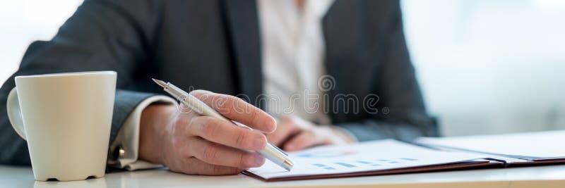 Imagen amplia de la visión de un empresario que revisa el informe de negocios fotografía de archivo