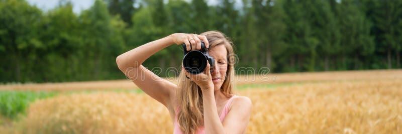 Imagen amplia de la visión de un fotógrafo de sexo femenino joven que toma una foto imagen de archivo