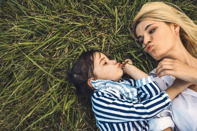Imagen antedicha de la visión de la mujer hermosa que juega con su niña linda en la hierba verde al aire libre Madre e hija bonit fotografía de archivo