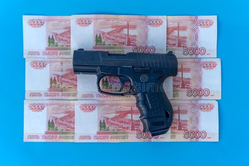 Imagen ascendente cercana de la pistola y de las rublos de dinero Gualterio y rublos en un primer azul del fondo imagenes de archivo