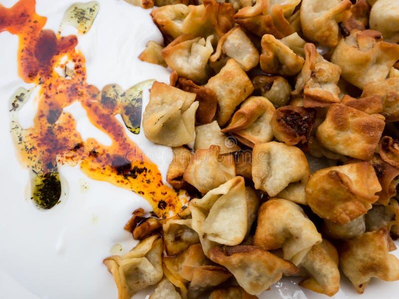 Imagen ascendente cercana de Manti turco frito con la pimienta roja, la salsa de tomate, el yogur y la menta Placa de la comida t imagen de archivo