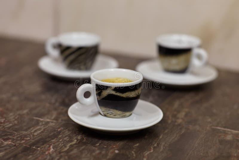 Imagen ascendente cercana de tres pequeños tazas y platillos, con café express del café, con diseño del modelo del tigre, en el f imagen de archivo libre de regalías