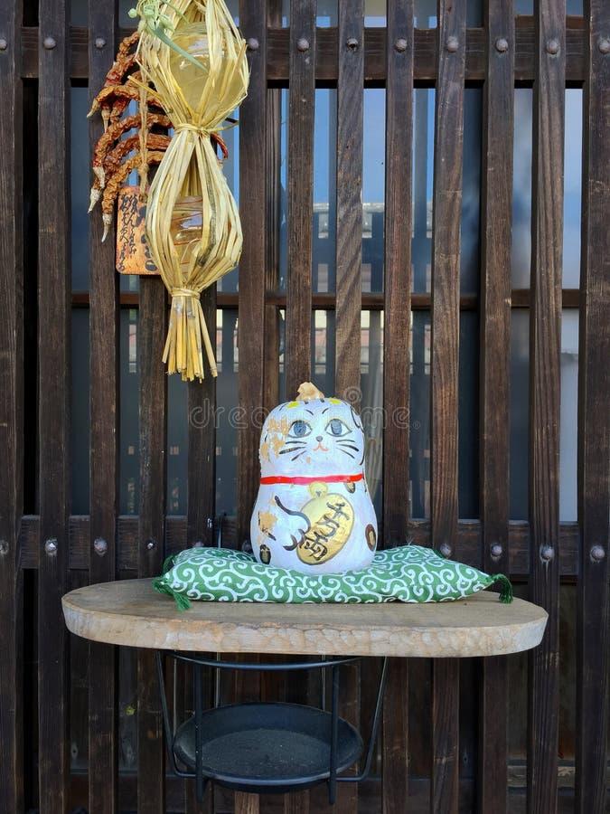 Imagen ascendente cercana de un pequeño gato japonés como la estatua de la porcelana fotografía de archivo