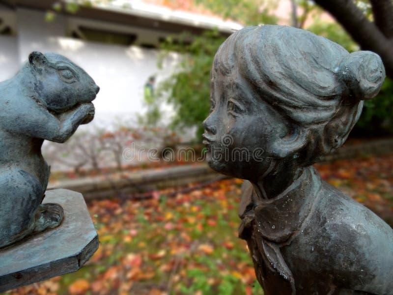 Imagen ascendente cercana de una estatua de bronce que figura a una muchacha que admira una ardilla foto de archivo libre de regalías