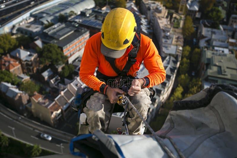 Imagen ascendente cercana del trabajador de sexo masculino de los trabajos del acceso de la cuerda que lleva el casco amarillo, c foto de archivo