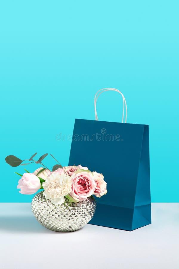 Imagen ascendente falsa con las flores color de rosa en florero cerca del soporte de papel del bolso del regalo en fondo azul Ima imágenes de archivo libres de regalías