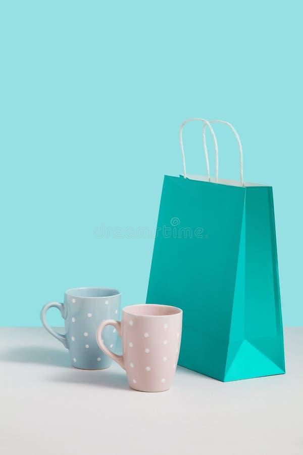 Imagen ascendente falsa con tender las tazas del t? cerca del soporte de la bolsa de papel en fondo azul Imagen del concepto del  imagen de archivo libre de regalías