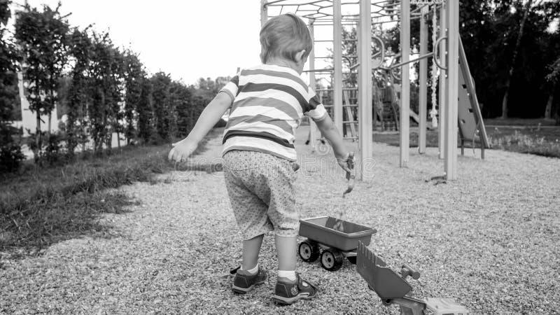 Imagen blanco y negro de 3 años del niño pequeño que se sienta en la salvadera en el palyground y que juega con el camión del jug fotografía de archivo libre de regalías