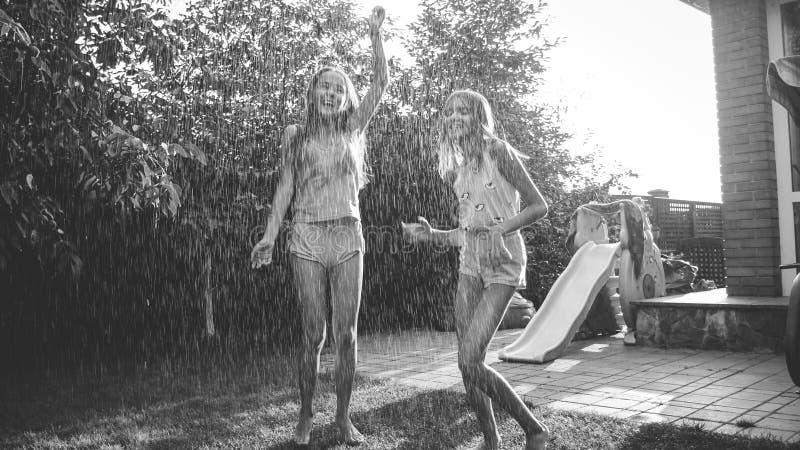 Imagen blanco y negro de dos muchachas de risa felices que gozan de la lluvia caliente del verano en el jard?n Familia que juega  imagenes de archivo