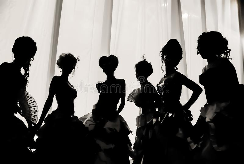 Imagen blanco y negro de la silueta de muchachas y de mujeres en trajes del carnaval y vestidos de bola en el teatro en el behin  fotos de archivo libres de regalías