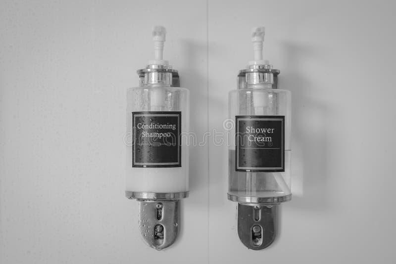 Imagen blanco y negro de las botellas poner crema de condicionamiento del champú y de la ducha que fijan en estante del metal en  imagenes de archivo