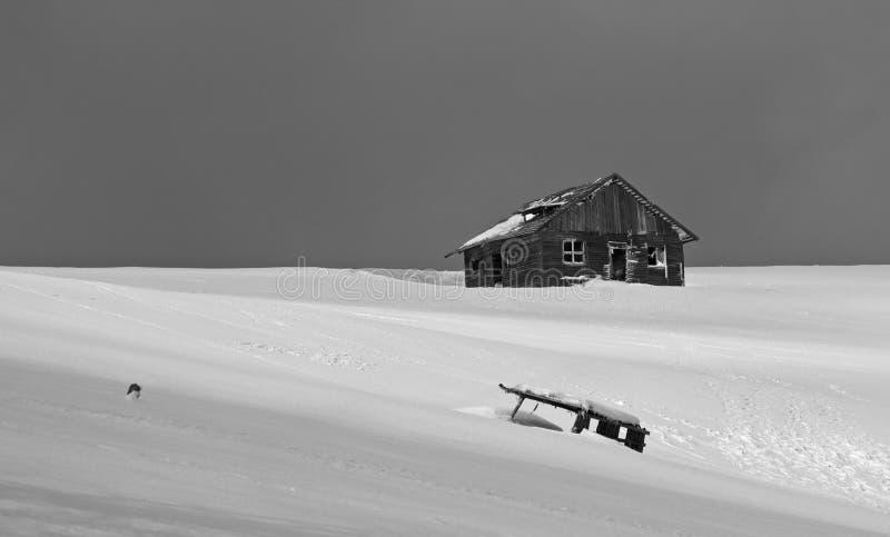 Imagen blanco y negro de una cabaña abandonada del pastor en las montañas durante invierno con nieve fotografía de archivo