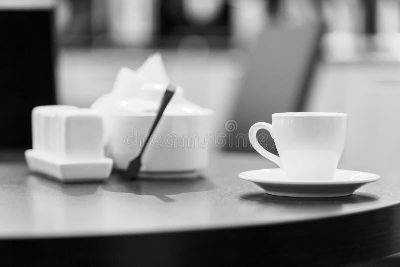 Imagen blanco y negro de una taza de té del café en la mesa redonda de madera en restaurante moderno del café y fondo borroso imagen de archivo libre de regalías