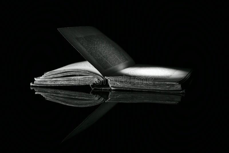 Imagen blanco y negro del alto contraste de un libro viejo en superficie reflexiva negra fotografía de archivo libre de regalías