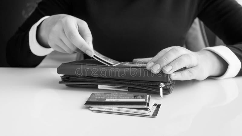 Imagen blanco y negro del primer de la empresaria que pone tarjetas de crédito en cartera imágenes de archivo libres de regalías
