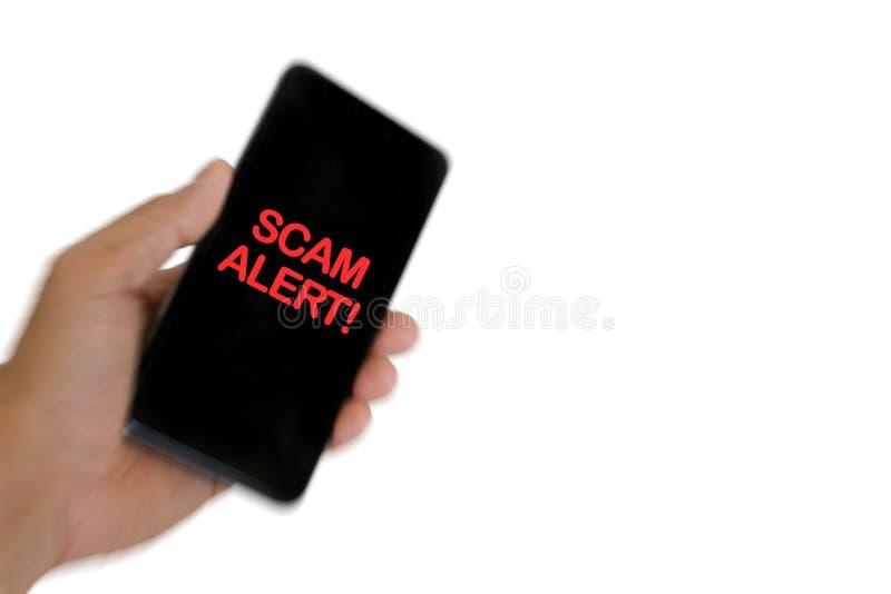Imagen borrosa de la mano que sostiene el teléfono móvil con ALARMA de la palabra SCAM foto de archivo libre de regalías