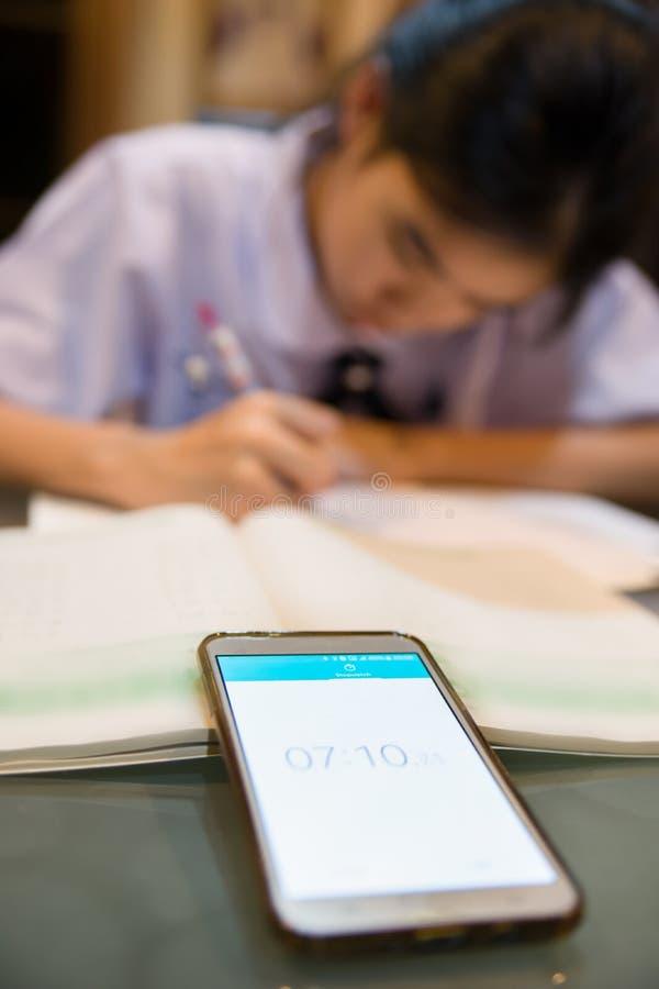 Imagen borrosa de la muchacha asiática que hace la preparación mientras que siendo tiempo por a foto de archivo