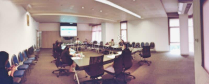 Imagen borrosa de los hombres de negocios y del estudiante que se sientan en la sala de conferencias, sala de reunión para el sem fotografía de archivo