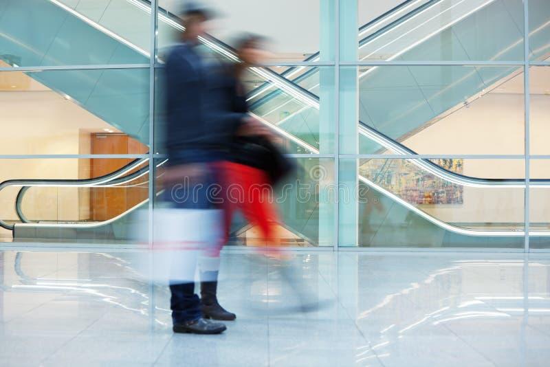 Imagen borrosa de pares jovenes en el edificio de oficinas foto de archivo