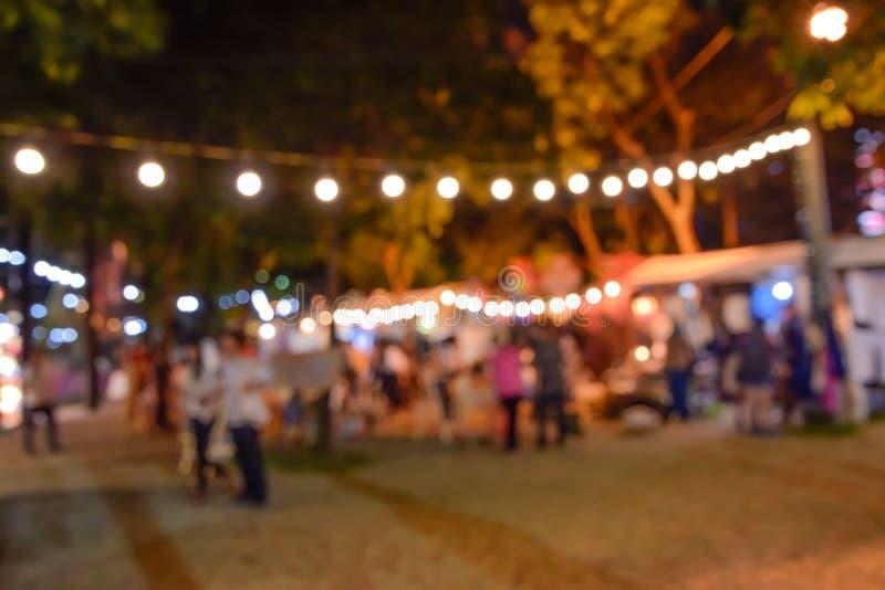 Imagen borrosa - Defocus de la gente que camina alrededor del festival del turismo de la noche en un parque en Bangkok, Tailandia imagenes de archivo