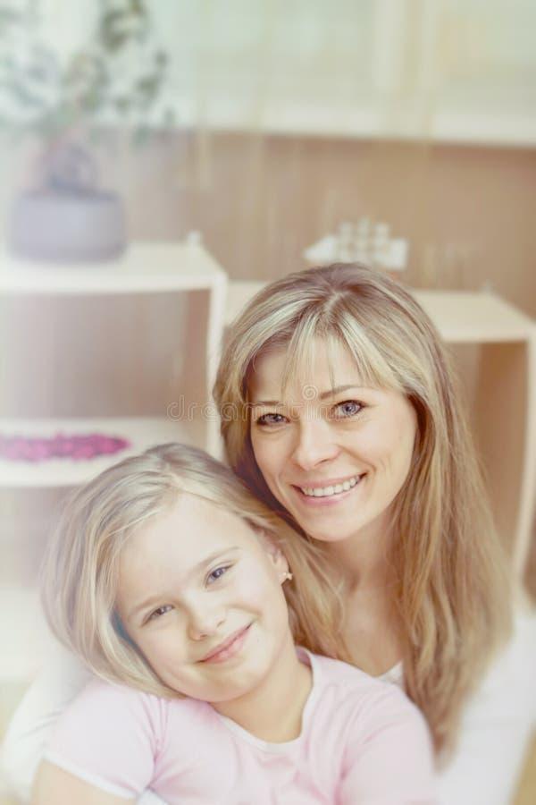 Imagen brillante de abrazar la madre y a la hija imagen de archivo