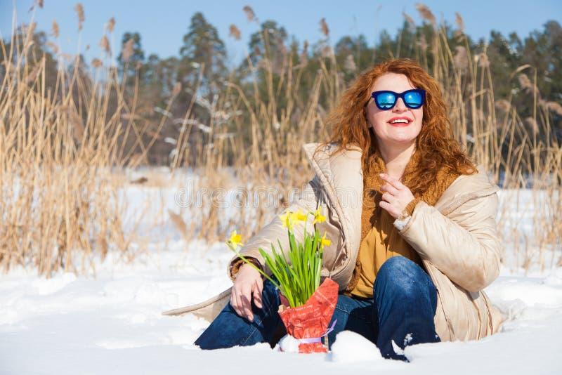 Imagen brillante de la mujer elegante carismática que se sienta en nieve acumulada por la ventisca foto de archivo