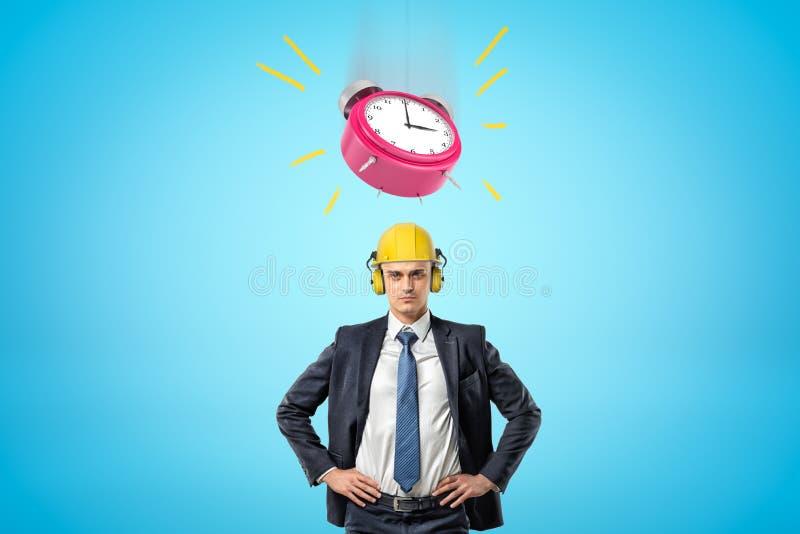 Imagen cintura-profunda delantera de la situación del hombre de negocios, manos en las caderas, casco amarillo que lleva con el s foto de archivo libre de regalías