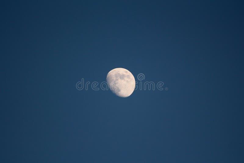 Imagen clara de la luna en la última puesta del sol retirada de patio trasero de la casa de la familia en el cielo azul marino imágenes de archivo libres de regalías