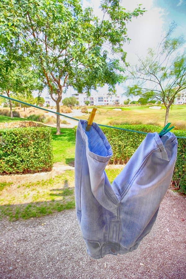 Imagen colorida brillante de los pantalones cortos del dril de algodón o de los vaqueros que cuelgan hacia fuera al Dr. fotos de archivo libres de regalías