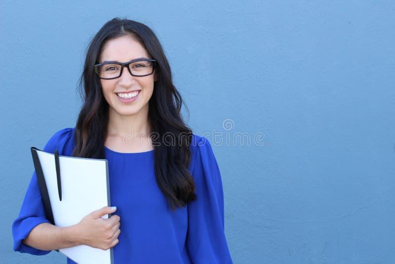 Imagen común del estudiante universitario de sexo femenino aislada en fondo azul fotos de archivo libres de regalías