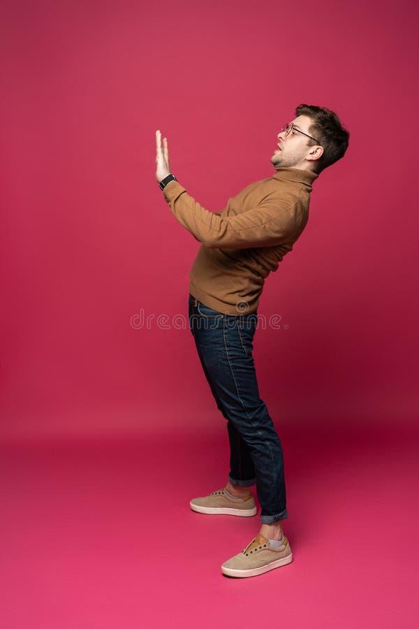 Imagen completa del cuerpo de un hombre casual joven que presenta algo en fondo rosado imagen de archivo libre de regalías