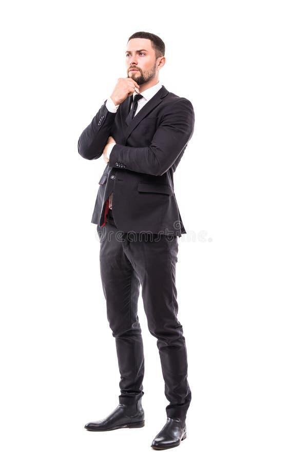 Imagen completa del cuerpo de un hombre de negocios joven sonriente que se sostiene la barbilla y que piensa en el fondo blanco fotografía de archivo libre de regalías