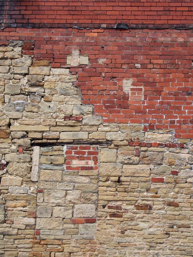 Imagen completa del marco de una pared vieja grande hecha de ladrillos y de piedra mezclados con muchas reparaciones remendadas y foto de archivo