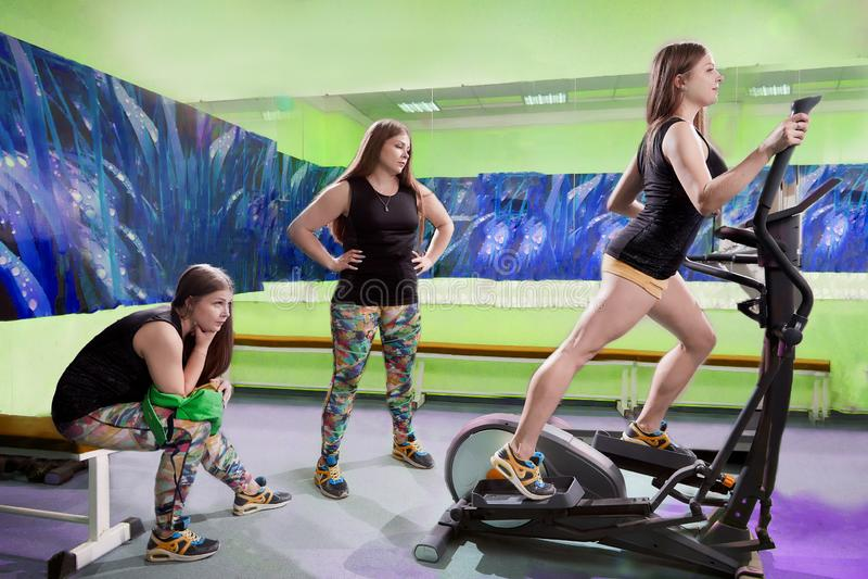Imagen compuesta con la mujer que está en gimnasio en tres versiones Dos muchachas gordas y una muchacha delgada Concepto de moti fotografía de archivo libre de regalías