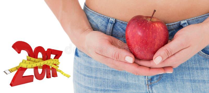 imagen compuesta 3D de la mujer del ajuste que se coloca con la manzana roja fotos de archivo