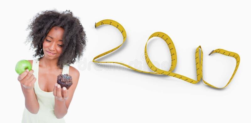imagen compuesta 3d de la mujer joven que vacila apenas entre un mollete y una manzana imagen de archivo libre de regalías