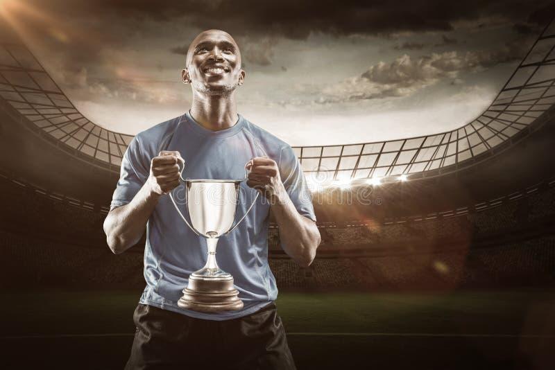 Imagen compuesta 3D del atleta feliz que sostiene el trofeo que mira para arriba fotografía de archivo libre de regalías