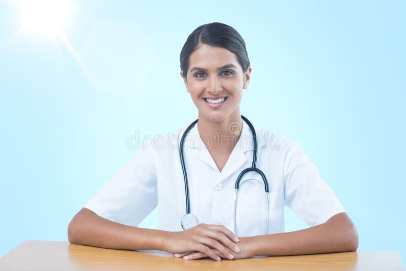 Imagen compuesta 3d del retrato del doctor de sexo femenino sonriente que se sienta en el escritorio imagen de archivo