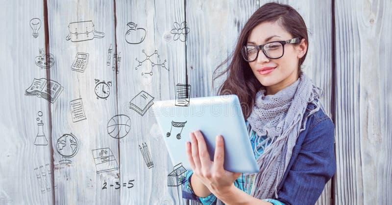 Imagen compuesta de Digitaces de la mujer que usa la tableta con los iconos en primero plano imagenes de archivo