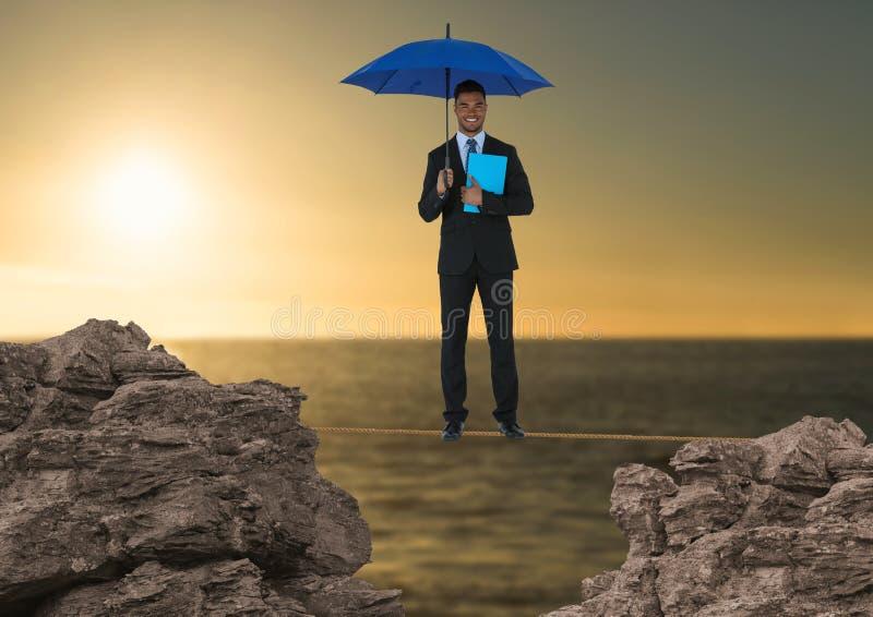 Imagen compuesta de Digitaces del hombre de negocios que se coloca en la cuerda que sostiene el diario con el paraguas azul en me fotografía de archivo