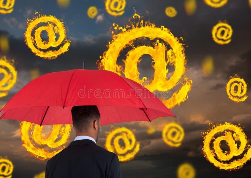 Imagen compuesta de Digitaces del hombre de negocios que sostiene el paraguas rojo que se coloca en medio de la quema en el símbo fotografía de archivo