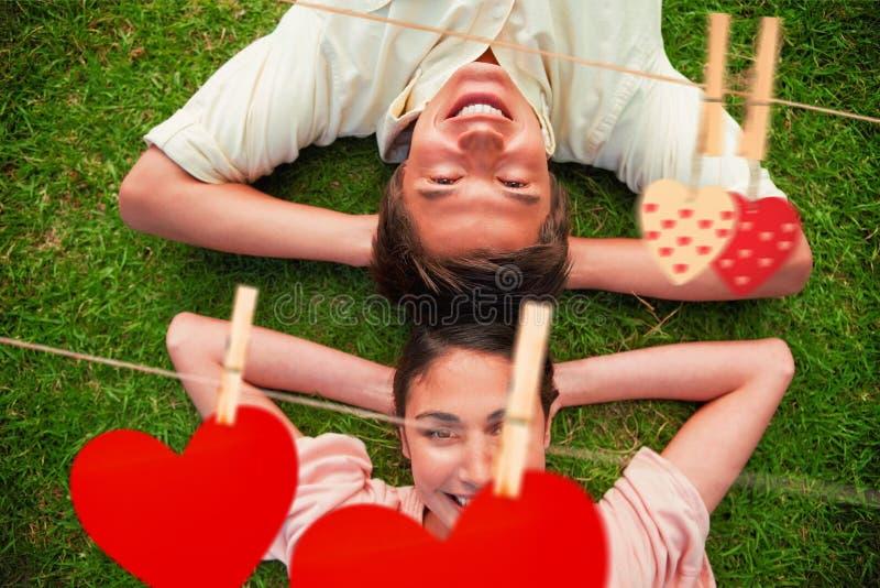 Imagen compuesta de dos amigos que sonríen mientras que miente comparativo con ambas manos detrás de su cuello libre illustration