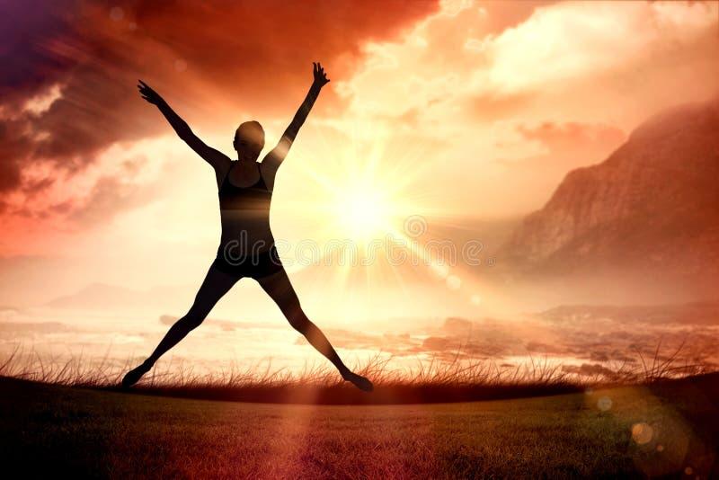 Imagen compuesta de integral de un salto deportivo de la mujer joven foto de archivo libre de regalías