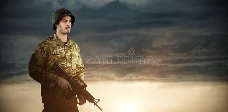 Imagen compuesta de integral del soldado que sostiene el rifle imagen de archivo