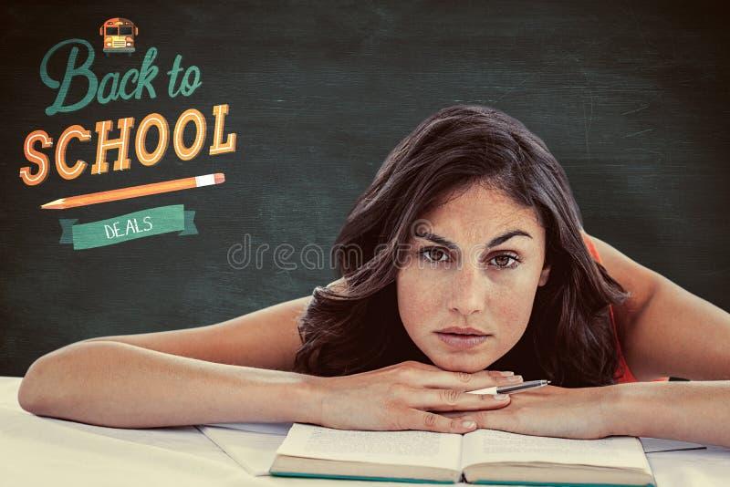 Imagen compuesta de la cabeza del estudiante que frunce el ceño en sus libros foto de archivo libre de regalías