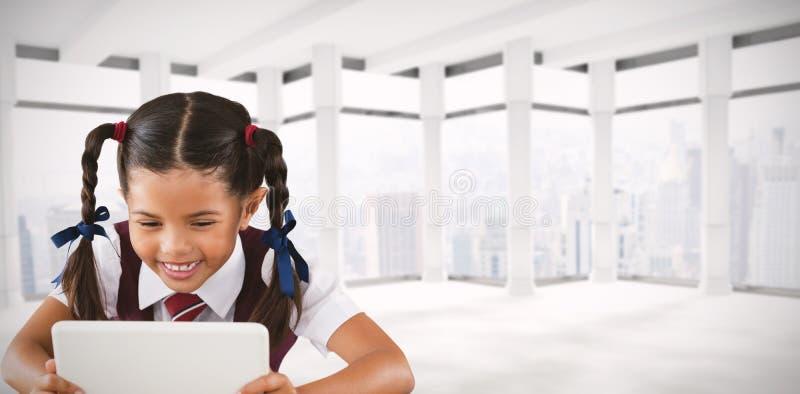 Imagen compuesta de la colegiala que usa la tableta digital en el escritorio imagen de archivo