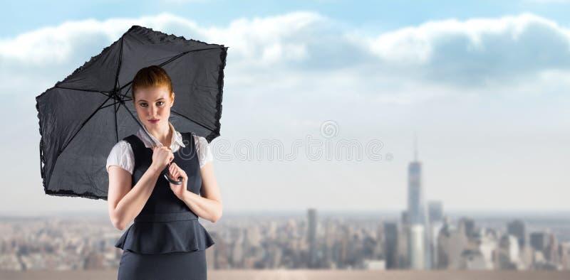 Imagen compuesta de la empresaria bonita del pelirrojo que sostiene el paraguas fotografía de archivo libre de regalías