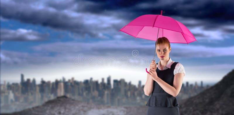 Imagen compuesta de la empresaria bonita del pelirrojo que sostiene el paraguas imagen de archivo
